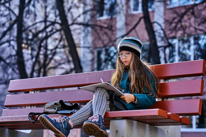 A teenager girl in glasses, a coat and a knitted hat sits on a bench in the park and draws a drawing on paper. Close-up. stock photo