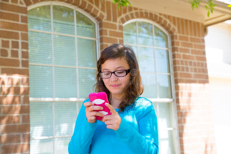Teenager girl with glasses playing with smartphone royalty free stock photography