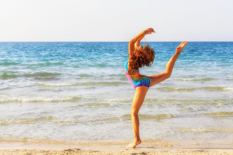Teenager girl during gymnastic workout on the beach royalty free stock photography