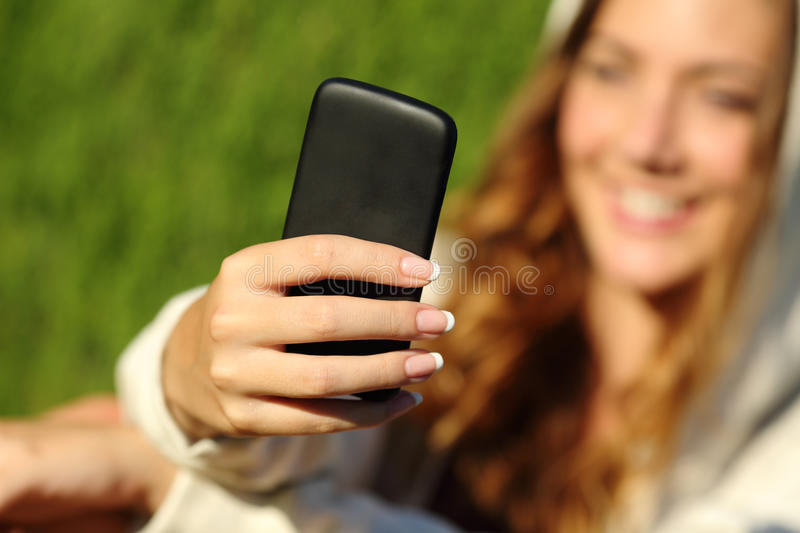Teenager girl hand using a smart phone with her face in the background. Teenager girl hand using a smart phone with her face and green nature in the background royalty free stock photo
