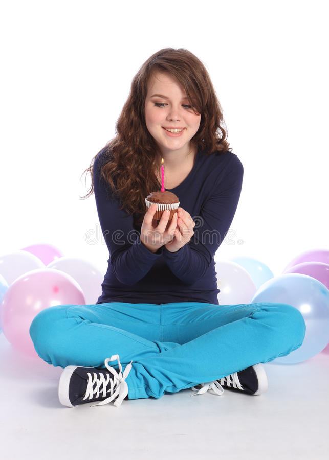 Teenager girl happy birthday chocolate cake. Pretty teenager girl celebrates happy birthday with a chocolate cup cake and single pink candle, sitting among party stock photo