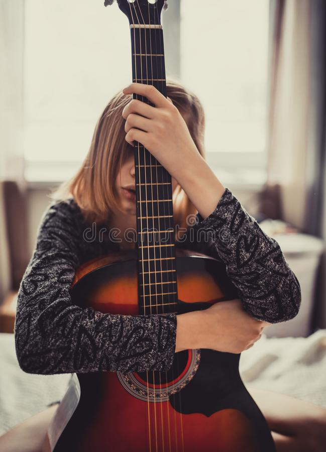 Teenager girl hiding behind guitar royalty free stock images