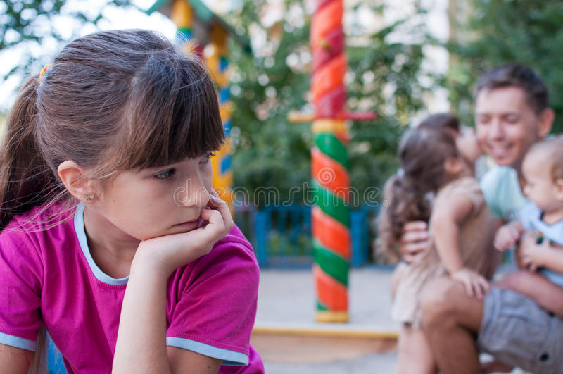 Teenager girl jealous of her younger sister and brother. Teenager girl annoyed with her family stock image