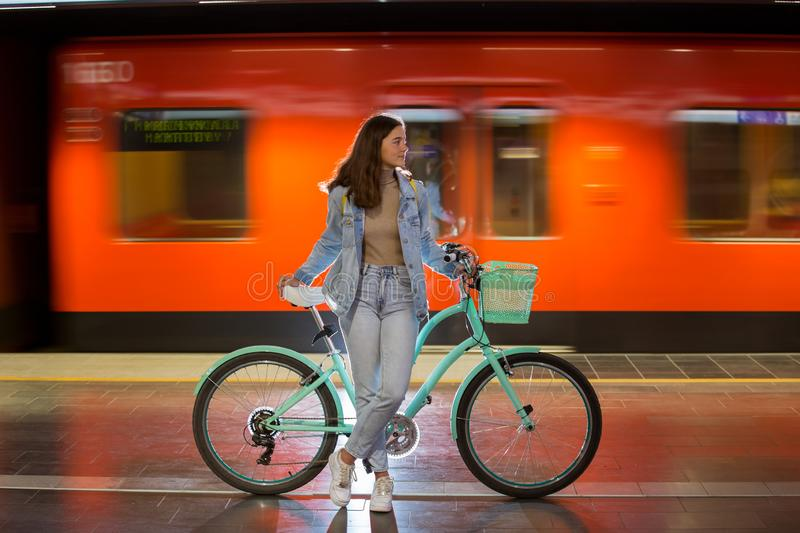 Teenager girl in jeans with yellow backpack and bike standing on metro station stock photography