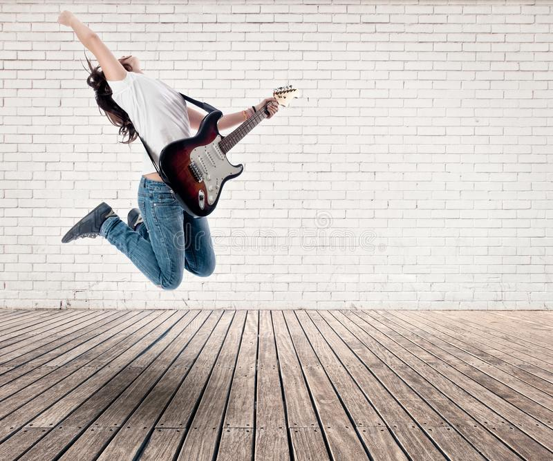Teenager girl jumping with electric guitar. On a room stock images