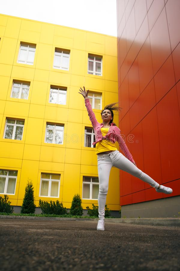 Teenager girl jumping in hip hop style over textured background stock photo