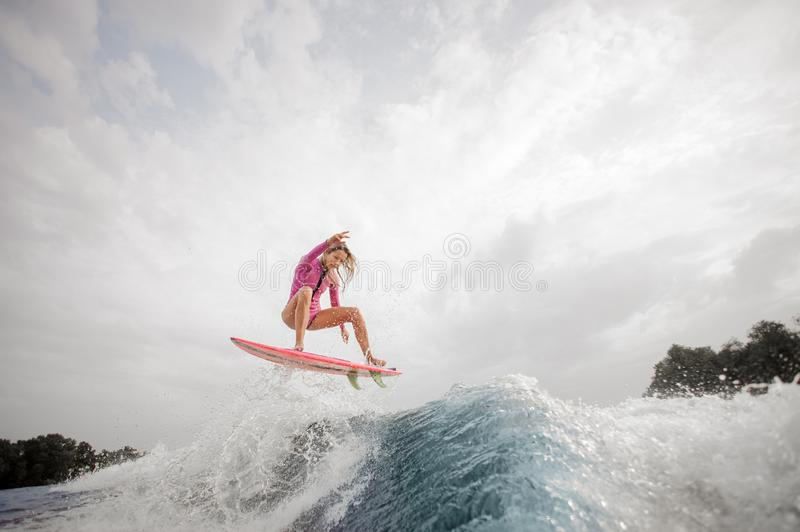 Teenager girl jumping on the orange wakeboard stock photo