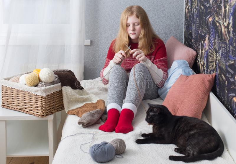 Teenager girl knits at home stock image