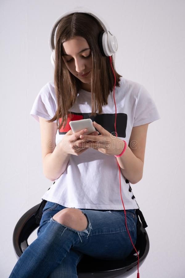 Teenager girl listens to music on headphone and writes message on cell phone isolated on white background royalty free stock image