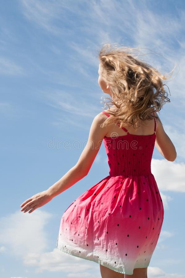 Teenager girl with long blonde hair standing back in beautiful summer dress stock images