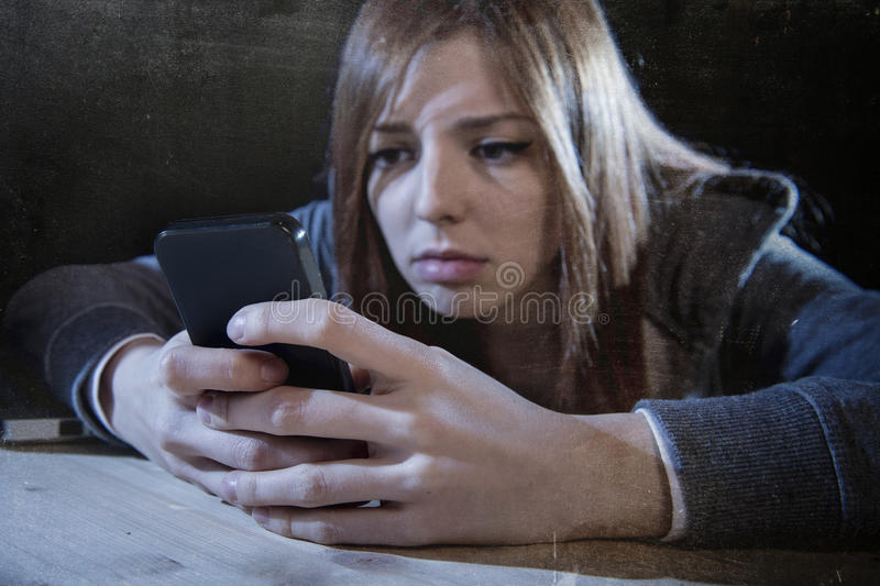 Teenager girl looking worried and desperate to mobile phone as internet stalked victim abused cyberbullying stress. Young scared teenager girl looking worried stock image