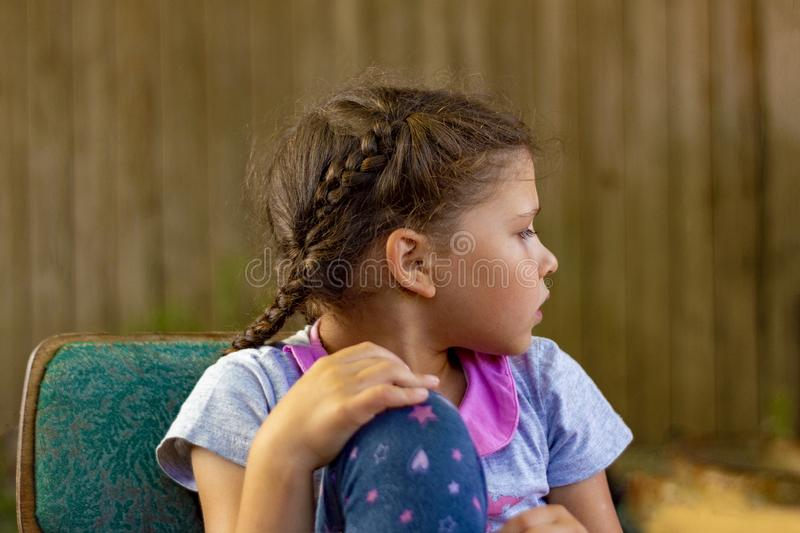 Teenager girl with pigtails sits on   vintage chair. I turned my head away from  camera. One hand on raised knee. Discontent. stock photo