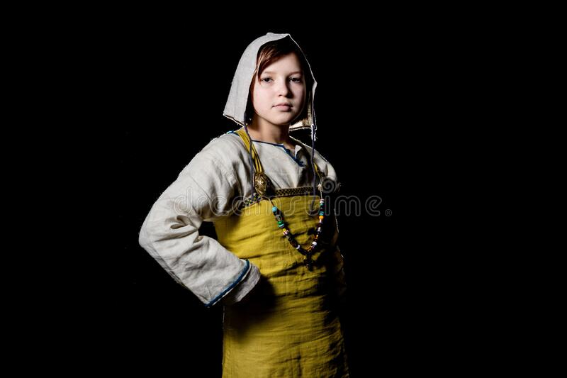 Teenager girl posing in ancient Viking clothes. Half growth, hands on hips stock image