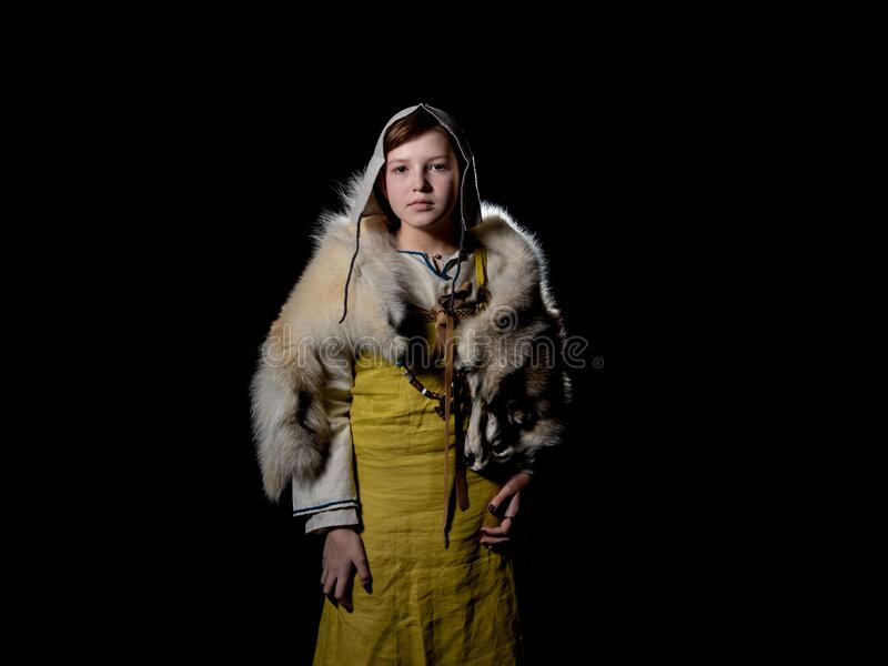 Teenager girl posing in ancient Viking clothes - Hangerok. On her shoulders is the skin of a wolf. half height portrait. Portrait of a Viking teenage girl royalty free stock photos