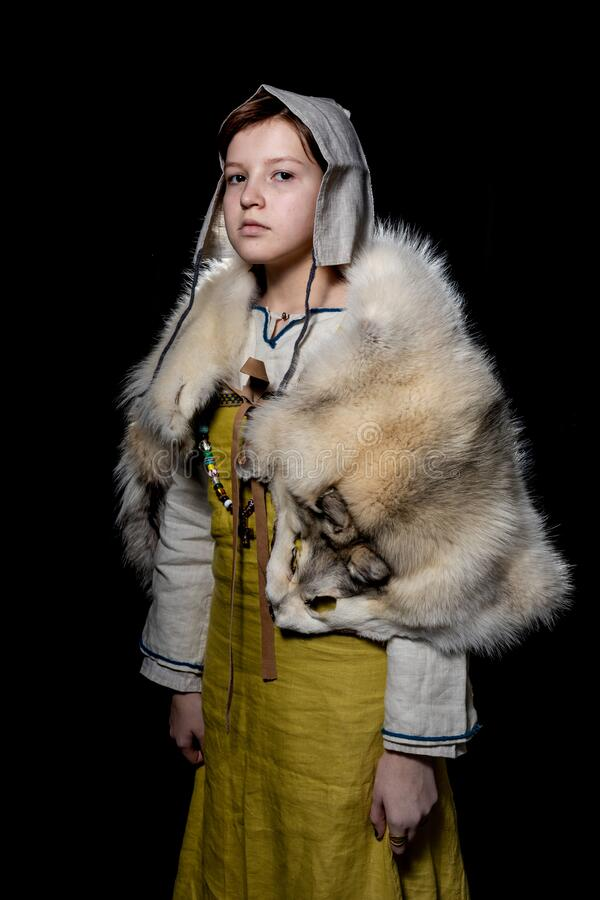 Teenager girl posing in ancient Viking clothes - Hangerok. On her shoulders is the skin of a wolf. Half-turn portrait. Portrait of a Viking teenage girl dressed royalty free stock photography
