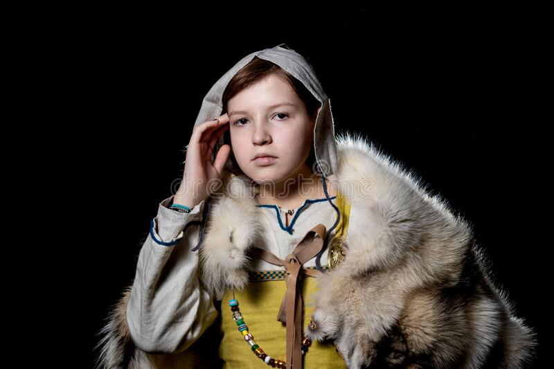 Teenager girl posing in ancient Viking clothes - Hangerok. On her shoulders is the skin of a wolf. The girl`s face expresses anxie. Portrait of a Viking teenage stock photos