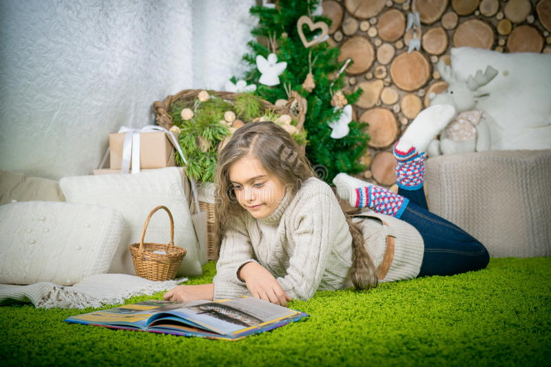 Teenager girl reading a book. Vintage portrait of cute school girl reading a book in cold day. Girl in sweater lying on her stomach reading a book at home in royalty free stock photography
