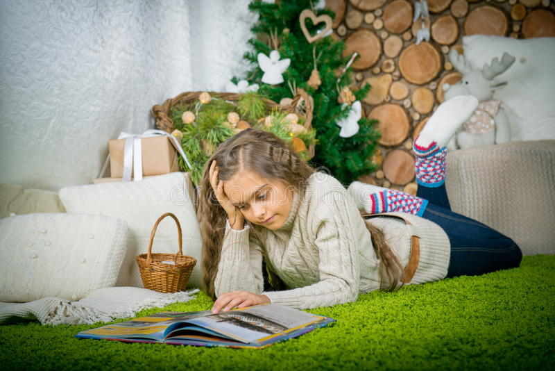Teenager girl reading a book. Vintage portrait of cute school girl reading a book in cold day. Girl in sweater lying on her stomach reading a book at home in royalty free stock images