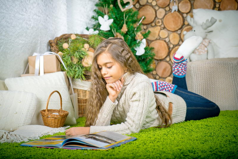 Teenager girl reading a book. Vintage portrait of cute school girl reading a book in cold day. Girl in sweater lying on her stomach reading a book at home in royalty free stock photos