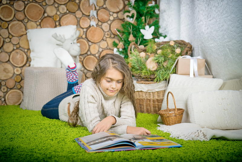 Teenager girl reading a book. Vintage portrait of cute school girl reading a book in cold day. Girl in sweater lying on her stomach reading a book at home in stock images