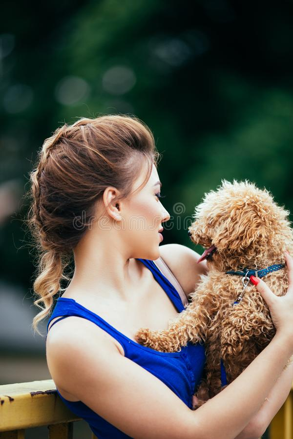Teenager girl with red poodle. Portrait of beautiful smiling young woman with her little red poodle puppy stock images