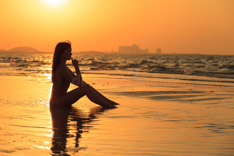 Teenager girl relax on the beach in sunset royalty free stock photography