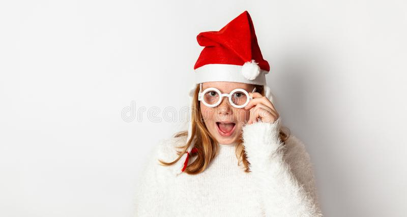 Teenager girl in santa christmas hat holds hand by glasses and surprised wow, isolated on white background stock image
