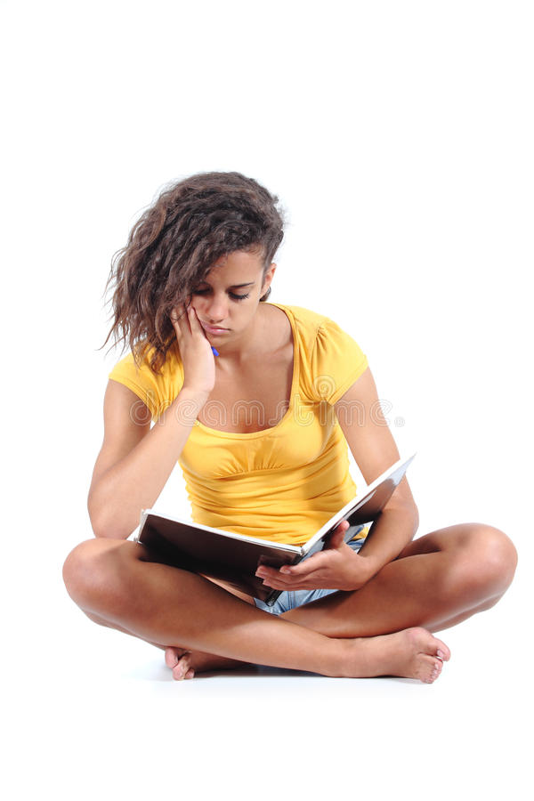 Teenager girl sitting and bored studying stock photo