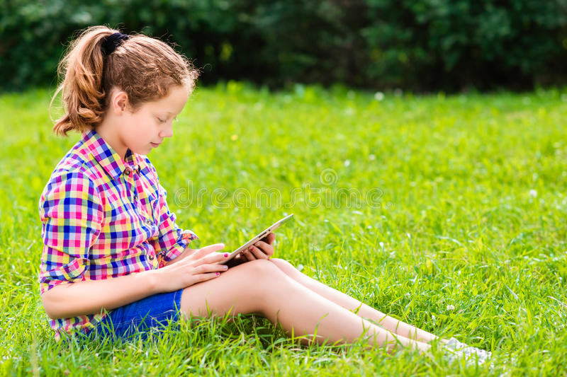 Download Teenager Girl Sitting On The Grass With Digital Tablet On Her Knees Stock Image - Image: 32994417
