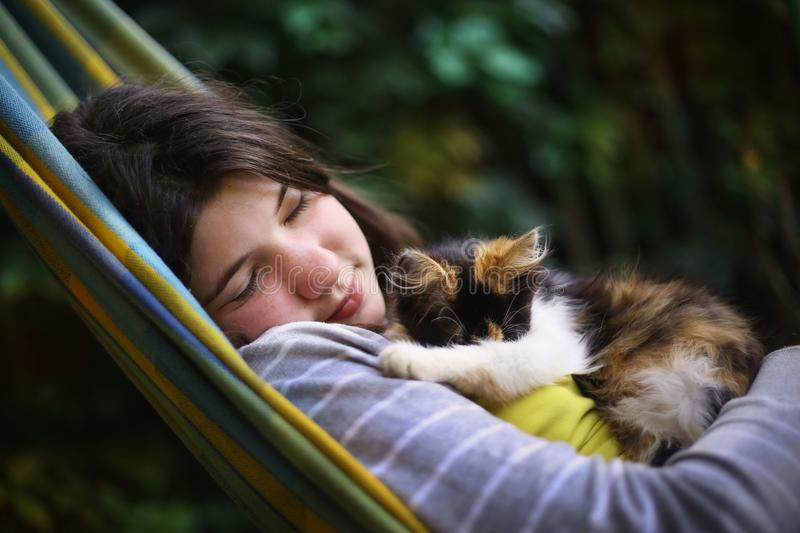 Teenager girl sleeping with little three color kitten in hammock royalty free stock images