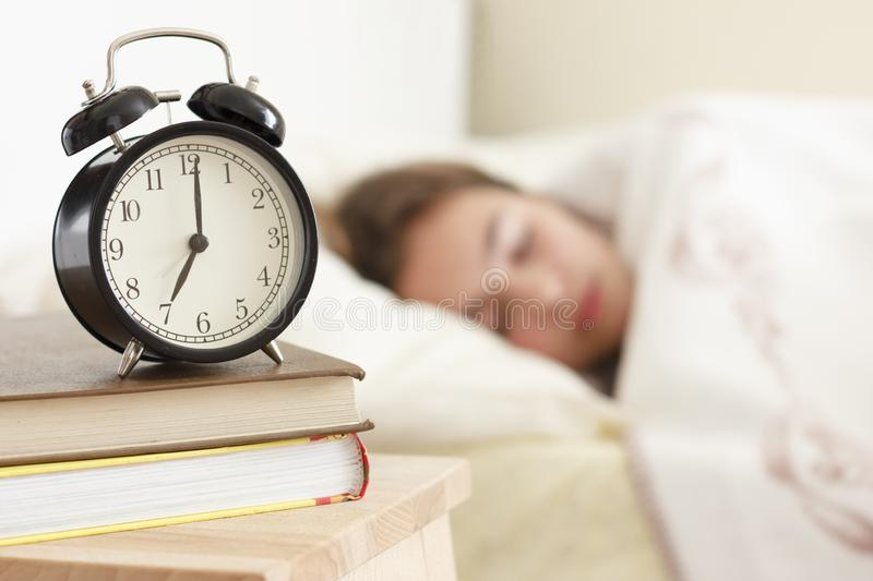 Teenager girl sleeping in a white bed. Alarm clock in the foreground on a pile of books. Teenager girl sleeping in a white bed. Alarm clock in the foreground on stock image