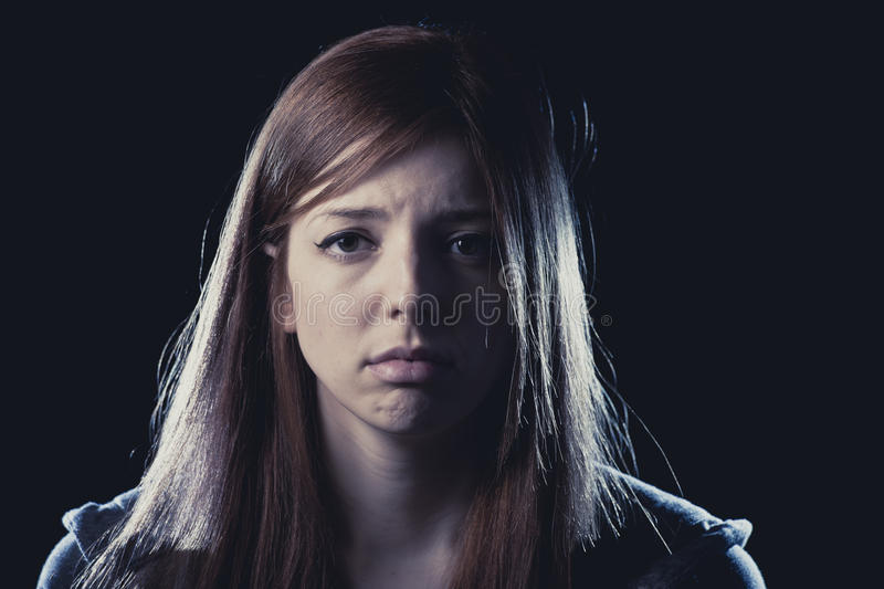 Teenager girl in stress and pain suffering depression sad and scared in fear face expression. Lonely young teenager girl in stress and pain suffering depression stock photo