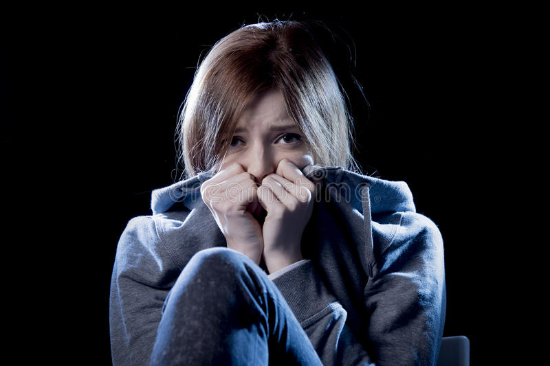Teenager girl in stress and pain suffering depression sad and scared in fear face expression. Lonely young teenager girl in stress and pain suffering depression royalty free stock photography