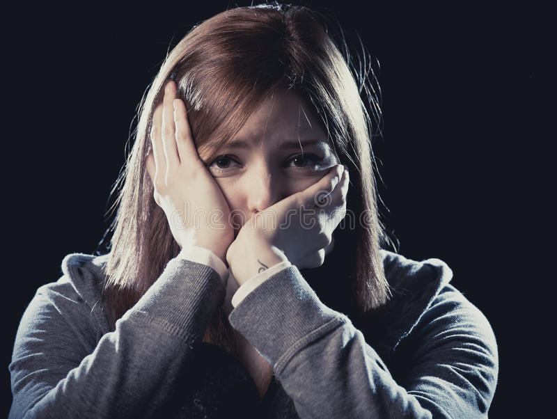 Teenager girl in stress and pain suffering depression sad and scared in fear face expression. Lonely young teenager girl in stress and pain suffering depression stock image