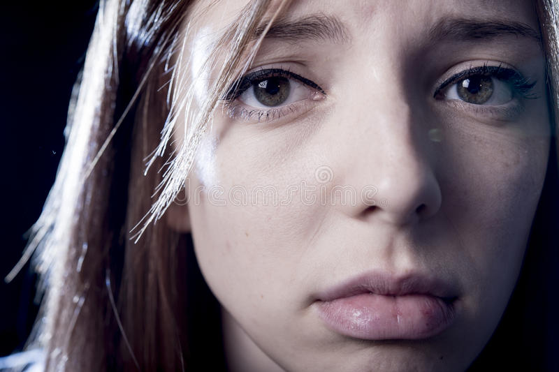 Teenager girl in stress and pain suffering depression sad and scared in fear face expression. Lonely young teenager girl in stress and pain suffering depression stock photography