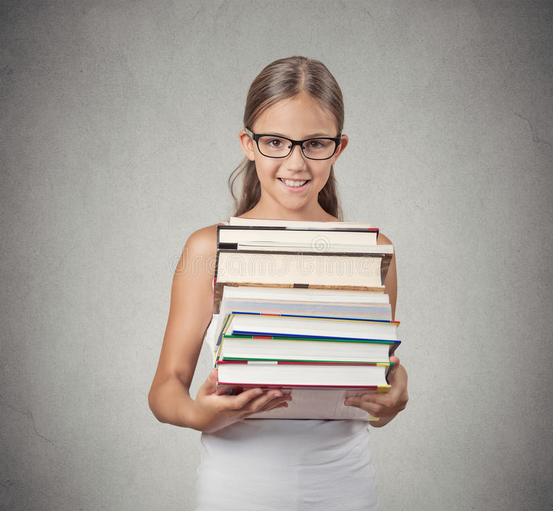Teenager girl student holding pile of books stock photos