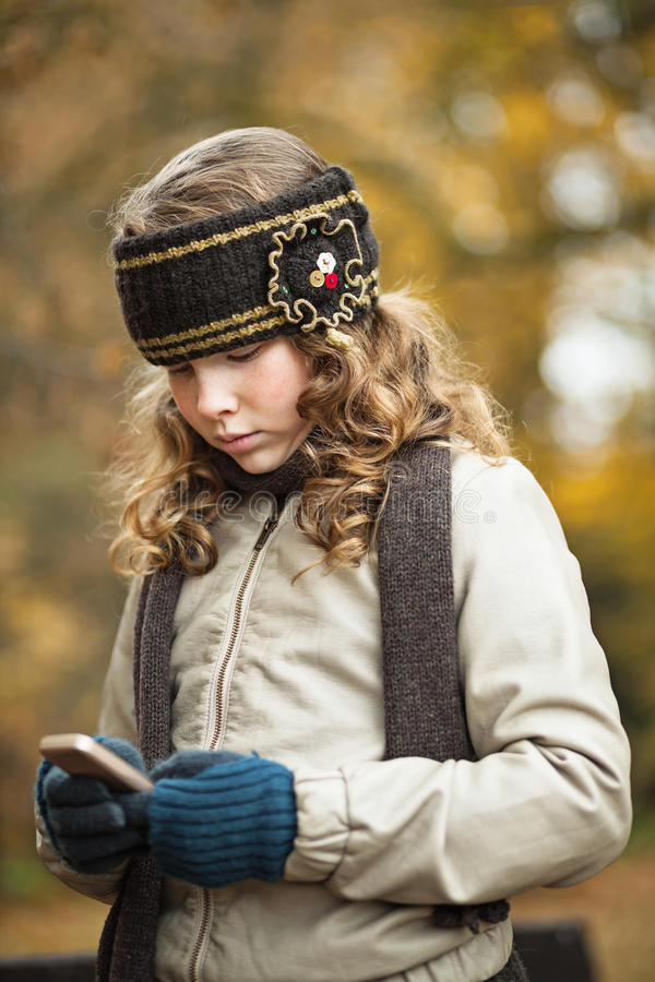 Teenager girl texting with cellphone in an autumn day royalty free stock photography