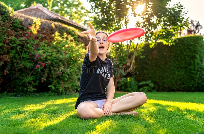 Teenager girl throwing frisbee sitting on green grass in garden backyard. stock images