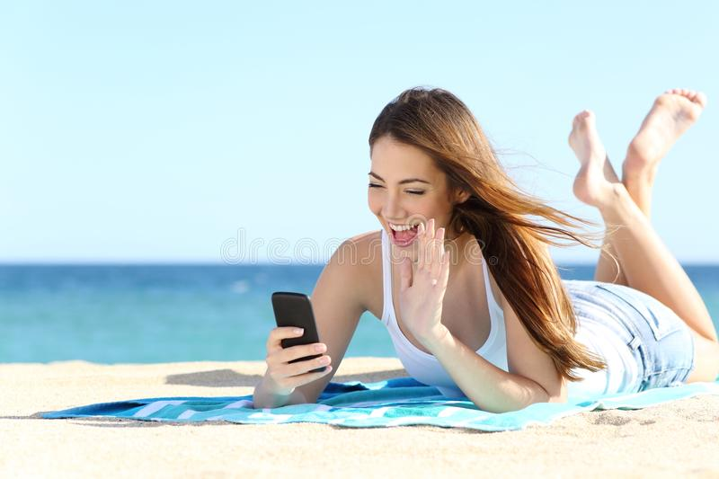 Teenager girl waving during a smart phone video call in vacations. With the sea in the background stock image