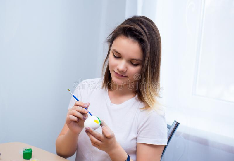 Teenager girl in a white T-shirt is painting Easter eggs at the table at home. white background.  stock image