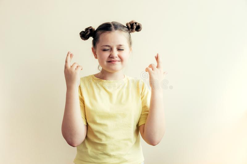Teenager girl in a yellow T-shirt crossed her fingers stock photo