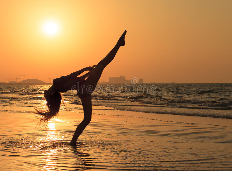 Teenager girl at yoga workout at orange sunset royalty free stock images