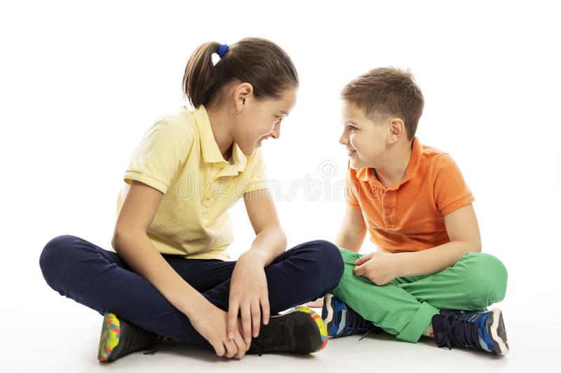 A teenager girl with a younger brother are sitting opposite each other. White background. Horizontal royalty free stock photo