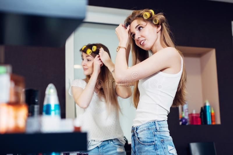 Teenager girls applying hair rollers on their long blond hair preparing to go out royalty free stock photography