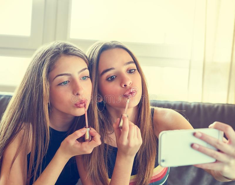 Teenager girls best friends makeup selfie camera. In smartphone make-up royalty free stock image