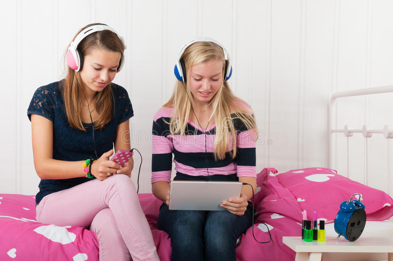 Teenager girls with tablet and smartphone stock photography
