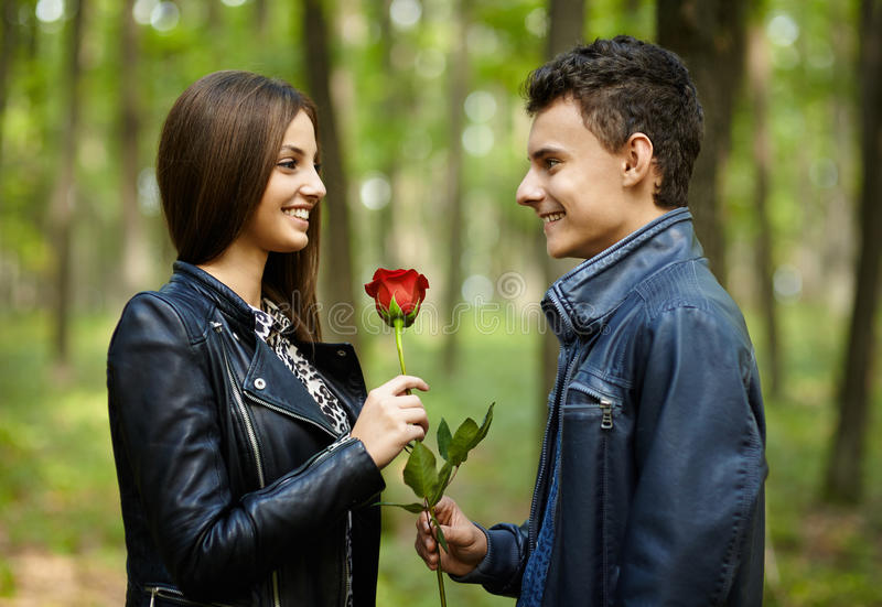 Teenager giving a flower to his girlfriend royalty free stock images