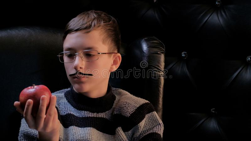A teenager in glasses with a glued-on mustache, wearing a sweater, sits in a black leather chair and looks thoughtfully at the red stock photos