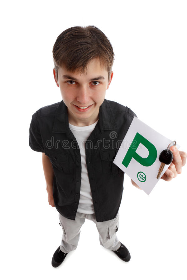 Teenager with green P licence plates. A teenage boy holds green P license plates and car key. He is smiling enthusiastically. Above view perspective. Standing on royalty free stock photos