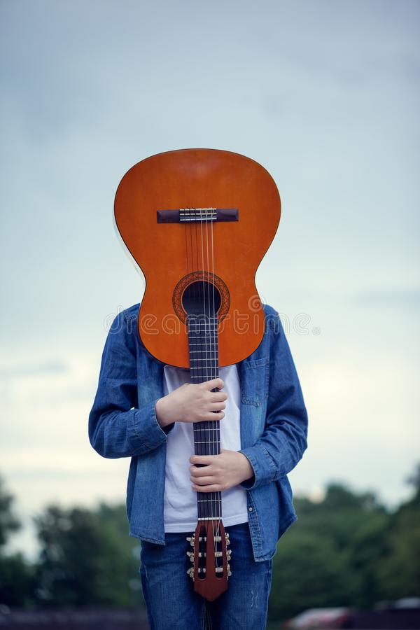 Teenager with a guitar instead of a head in the park. Crazy and cool young man with a guitar royalty free stock photography
